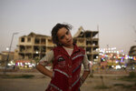 In this Thursday, Sept. 5, 2019, photo, Marwa, 10, poses for a portrait in a park near battle-ravaged buildings in Raqqa, Syria. Two years after the military offensive to oust the Islamic State group from its stronghold, Raqqa has been picking up the pieces. Officials say more than 800,000 people have returned to the city and its adjacent suburbs_ nearly eight times the residents who were left when the militants were finally expelled in Oct. 2017. (AP Photo/Maya Alleruzzo)