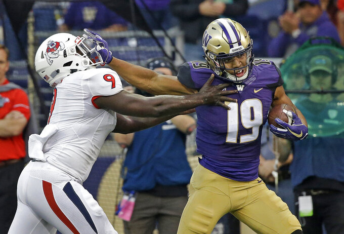 FILE - In this Sept. 16, 2017, file photo, Washington's Hunter Bryant (19) tries to fend off Fresno State's Jeffrey Allison as he runs after a pass reception for 50 yards in the first half of an NCAA college football game in Seattle. After spending more than half the season recovering from knee surgery in June, Bryant has provided a boost for the 10th-ranked Huskies' offense heading into Friday's Pac-12 championship game against No. 17 Utah.  (AP Photo/Elaine Thompson, File)