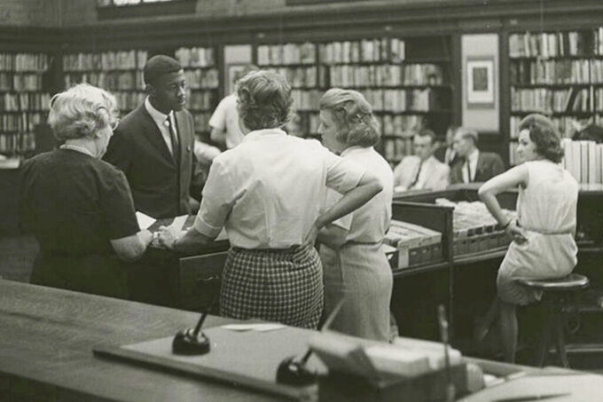 Miles College student Shelly Millender, standing in suit, is shown during an effort to desegregate the public library in Birmingham, Ala., on April 10, 1963. Millender, a Black Army veteran who helped peacefully desegregate an Alabama city's library with a sit-in protest in 1963, died on Saturday, July 17, 2021, according to the library and an obituary published by his family. He was 86.  (Birmingham News/Alabama Department of Archives and History via AP)