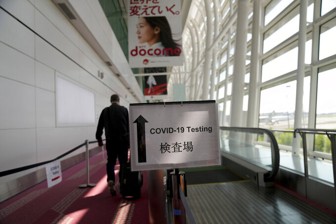 A sign directs passengers arriving in Tokyo, Monday, July 19, 2021, to get their COVID-19 tests before being allowed to enter the country. (AP Photo/Natacha Pisarenko)