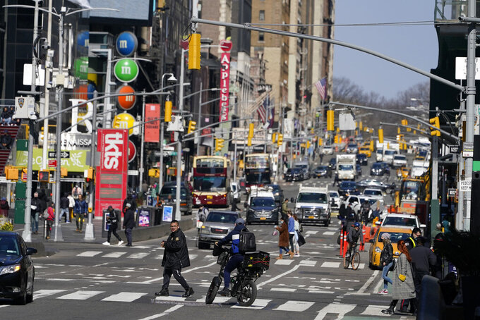 People enjoy a sunny day in Times Square in New York, Wednesday, March 10, 2021. After the virus descended on New York, the only sounds in the streets were wailing ambulance sirens. A year after the pandemic began, the nation's largest metropolis -- with a lifeblood based on round-the-clock hustle and bustle, push and pull -- is adapting and showing new life. (AP Photo/Seth Wenig)