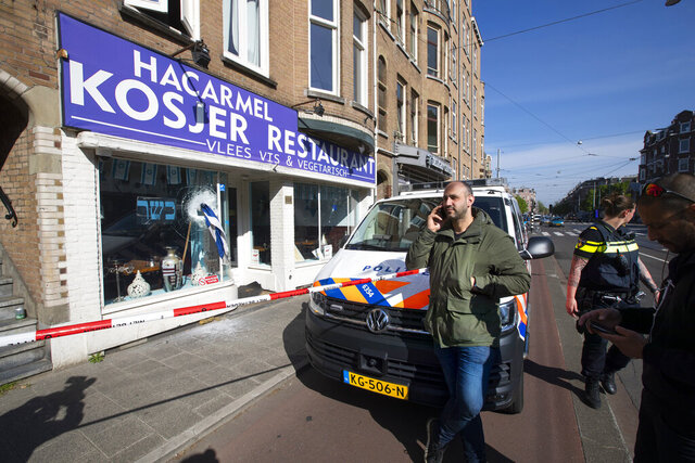 An Israeli flag sticks out of the window of HaCarmel kosher restaurant in Amsterdam, Netherlands, Friday, May 8, 2020, after a man smashed the window with the flagpole. The owner David Bar-On, center right, said his restaurant was vandalized for the sixth time in what appeared to be another anti-Semitic attack. (AP Photo/Peter Dejong)