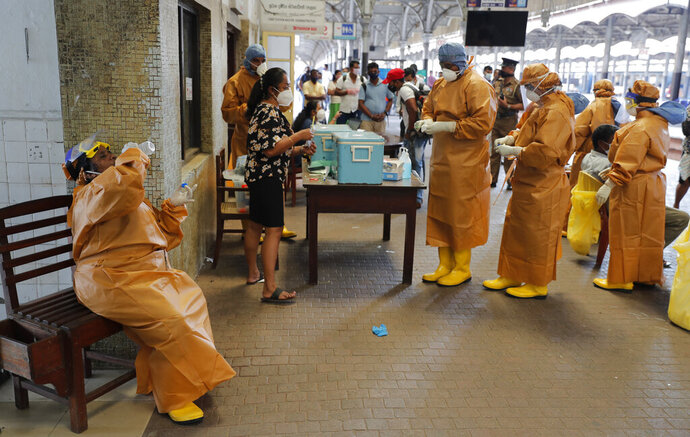 A health officer collecting swab samples from rail commuters to test for COVID-19 drinks water during a break at a railway station in Colombo, Sri Lanka, Monday, Oct. 12, 2020. (AP Photo/Eranga Jayawardena)