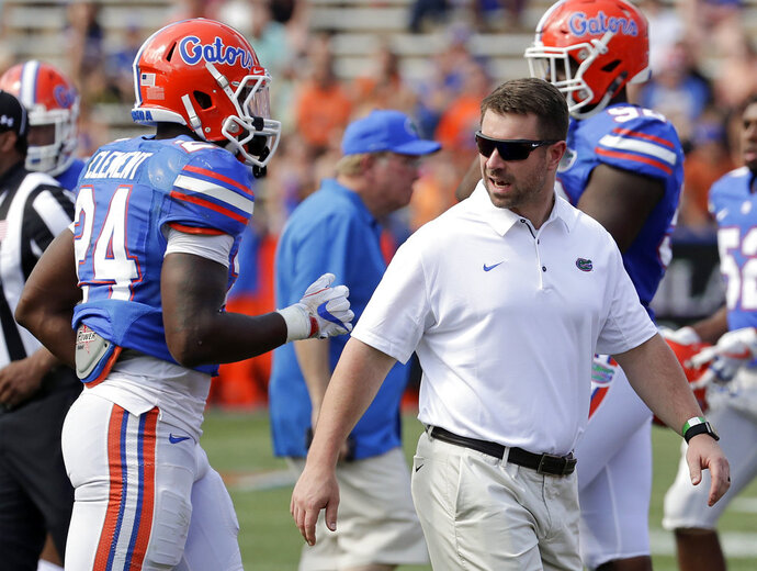 Florida's Nick Savage, right, director of football strength and conditioning, talks with running back Iverson Clement (24) during an NCAA spring college football intrasquad game, Saturday, April 14, 2018, in Gainesville, Fla. (AP Photo/John Raoux)