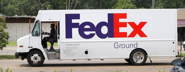 FILE - In this June 25, 2019, file photo, a FedEx Ground package van pulls into a business driveway in this north Jackson, Miss., facility. Amazon is banning its third-party merchants from using FedEx's ground service to deliver to Prime members, suggesting that it thinks the service is too slow to get packages to their destinations in time for Christmas. (AP Photo/Rogelio V. Solis, File)