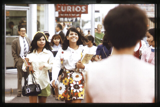 In this photo taken by Walter McDonald in 1969 and provided by the Albuquerque Museum, two young women walk on a sidewalk along Route 66 in Albuquerque, N.M. The photo, and other images from a street photography project that were taken in the late 1960s and early 1970s, are scheduled to go on display Dec. 21, 2019 until May 24, 2020, at the Albuquerque Museum in Albuquerque, N.M. (Albuquerque Museum via AP)