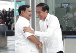Indonesian President Joko Widodo, right, greets his defeated election rival Prabowo Subianto during their meeting at a subway station in Jakarta, Indonesia, Saturday, July 13, 2019. Widodo and the former special forces general met for the first time since the divisive April poll, signaling a calming of political tensions in the world's third-largest democracy. (AP Photo/Dita Alangkara)
