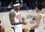 Phoenix Suns forward Torrey Craig, left, congratulates guard Devin Booker as time runs out in the second half of Game 4 of an NBA second-round playoff series against the Denver Nuggets, Sunday, June 13, 2021, in Denver. Phoenix won 125-118 to sweep the series. (AP Photo/David Zalubowski)