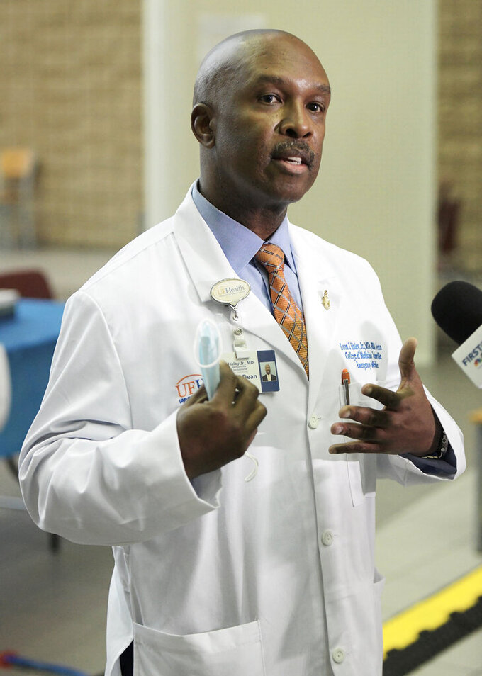 Dr. Leon Haley Jr. the CEO of UF Health Jacksonville talks with the media shortly before he received the first injection of the COVID-19 vaccine, Monday, Dec. 14, 2020, in Jacksonville, Fla. Haley, 56, who was lauded for his efforts in response to COVID-19, died in an accident involving a personal watercraft vehicle, officials said. Haley was ejected from a personal watercraft in Palm Beach Inlet on Saturday, July 24, 2021, the Florida Fish and Wildlife Conservation Commission said. (Bob Self/The Florida Times-Union via AP)