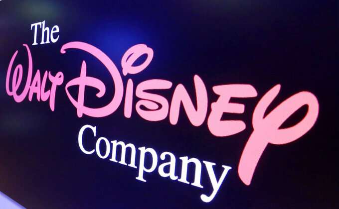 FILE - In this Aug. 7, 2017, file photo, The Walt Disney Co. logo appears on a screen above the floor of the New York Stock Exchange. The Walt Disney Co. turned a profit in 2021 in its most recent quarter as reopened parks provided a revenue bounce. Revenue in the parks and products division surged to $4.3 billion from $1.1 billion a year ago, as theme parks closed last year were open for part or all of this year's quarter. (AP Photo/Richard Drew, File)