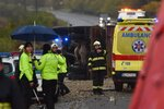 Firefighters, police and rescuers work the scene of a traffic accident involving a bus and a lorry on a road near the village of Malanta near Nitranske Hrnciarovce, Slovakia, Wednesday Nov. 13, 2019. A bus collided with a truck in Slovakia on Wednesday, killing at least a dozen people and injuring at least 20 more. Online news site tvnoviny.sk reported that the bus was carrying high school students.(Lukas Grinaj/TASR via AP)