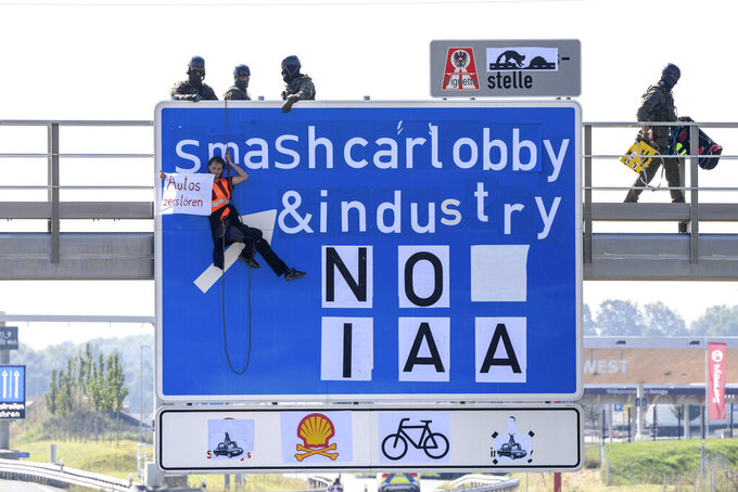 """An activist hangs from a gantry over the A9 motorway near Fürholzen in the direction of Munich during a banner campaign, holding a banner with the words """"Destroy cars"""" in his hands while police officers from a special task force get into position on the gantry, Tuesday, Sept.7, 2021. The activists have pasted over the traffic sign with the words """"smashcarlobby & industry - NO IAA"""". (Matthias Balk/dpa via AP)"""