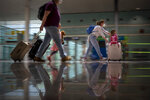 Tourists arrive at Barcelona airport, Spain, Monday, June 7, 2021. Spain is trying to ramp up its tourism industry by welcoming from Monday vaccinated visitors from most countries, as well as all Europeans who prove that they are not infected with the coronavirus. (AP Photo/Emilio Morenatti)