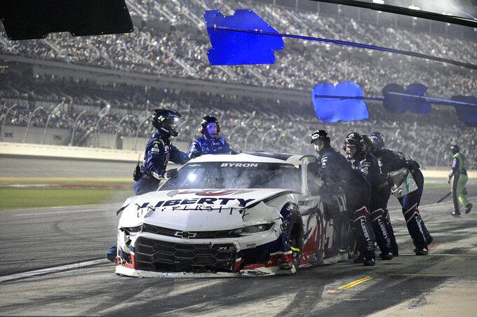 Crew members push William Byron's vehicle on pit road during a NASCAR Cup Series auto race at Daytona International Speedway, Saturday, Aug. 28, 2021, in Daytona Beach, Fla. (AP Photo/Phelan M. Ebenhack)