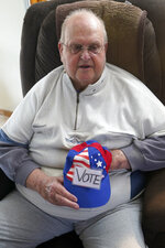 Charley Crabtree holds one of his hats at his home in Lawrence, Kan., Thursday, April 8, 2021. Crabtree was looking to help voters in nursing homes get absentee ballots delivered on time last year, so he picked up about 75 from at least 10 locations in his hometown of Lawrence. Republicans who control the Kansas Legislature want to make what he did a crime punishable by up to six months in jail. (AP Photo/Orlin Wagner)