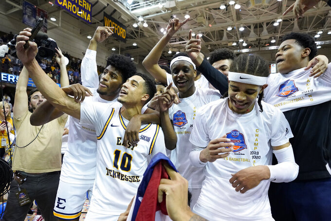 The East Tennessee State basketball team celebrates their win over Wofford for the NCAA men's basketball Southern Conference championship, Monday, March 9, 2020, in Asheville, N.C. (AP Photo/Kathy Kmonicek)