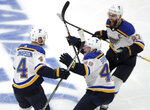 FILE - St. Louis Blues' Carl Gunnarsson (4), of Sweden, is congratulated by Ivan Barbashev (49), of Russia, and Alex Pietrangelo, right, after he scored the winning goal against the Boston Bruins during the first overtime period in Game 2 of the NHL hockey Stanley Cup Final in Boston, in this Wednesday, May 29, 2019, file photo. Blues defenseman Carl Gunnarsson announced his retirement Wednesday, June 23, 2021, after playing 12 NHL seasons and scoring one of the biggest goals in that franchise's history. (AP Photo/Charles Krupa, File)