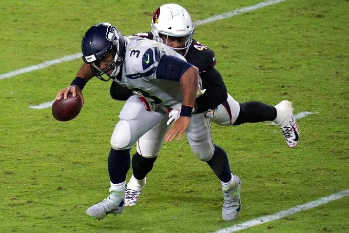 Seattle Seahawks quarterback Russell Wilson (3) is hit by Arizona Cardinals outside linebacker Haason Reddick (43) during the second half of an NFL football game, Sunday, Oct. 25, 2020, in Glendale, Ariz. (AP Photo/Ross D. Franklin)