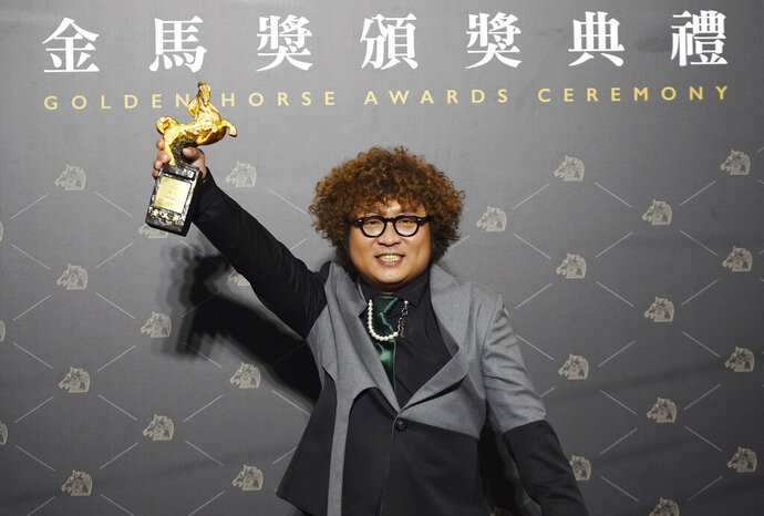 Taiwanese actor Nadow Lin holds his award for Best Supporting Actor at the 57th Golden Horse Awards in Taipei, Taiwan, Saturday, Nov. 21, 2020. Lin won for the film