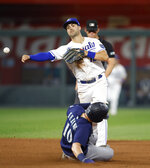 Kansas City Royals second baseman Whit Merrifield, top, throws to first base for a double play as Seattle Mariners' Jarred Kelenic (10) slides into second during the fifth inning of a baseball game at Kauffman Stadium in Kansas City, Mo., Saturday, Sept. 18, 2021. (AP Photo/Colin E. Braley)