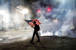 FILE - In this July 21, 2020, file photo, a Black Lives Matter protester carries an American flag as teargas fills the air outside the Mark O. Hatfield United States Courthouse in Portland, Ore. Once hailed as one of the most livable cities in the U.S., Portland, Oregon, is grappling with an uncertain future as it reaches a stunning benchmark: 100 consecutive nights of racial injustice protests marred by vandalism, chaos — and now, the killing of a supporter of President Donald Trump. (AP Photo/Noah Berger, File)