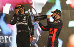 Mercedes driver Lewis Hamilton of Britain, left, and Red Bull driver Max Verstappen of the Netherlands stand on the winners podium after the Formula One Abu Dhabi Grand Prix in Abu Dhabi, United Arab Emirates, Sunday, Dec. 13, 2020. (AP Photo/Kamran Jebreili, Pool)