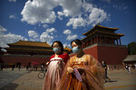 Women in period dress and wearing face masks to protect against the new coronavirus walk outside the entrance to the Forbidden City in Beijing, Wednesday, May 27, 2020. The Chinese People's Political Consultative Conference (CPPCC) concluded its session in Beijing on Wednesday, part of the annual meetings of China's two top legislative bodies. (AP Photo/Mark Schiefelbein)