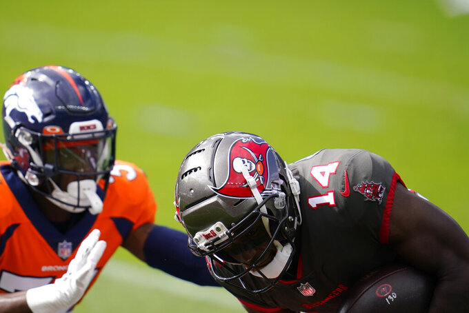 Tampa Bay Buccaneers wide receiver Chris Godwin, right, scores a touchdown as Denver Broncos defensive back Essang Bassey defends during the first half of an NFL football game Sunday, Sept. 27, 2020, in Denver. (AP Photo/David Zalubowski)