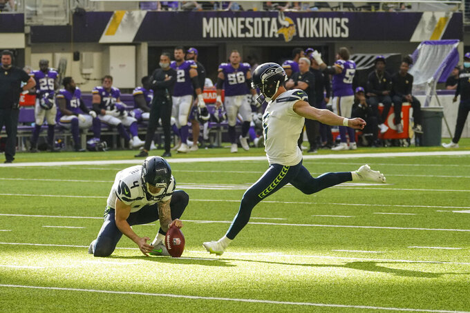Seattle Seahawks kicker Jason Myers (5) starts to boot a field goal from the hold of Michael Dickson in the first half of an NFL football game against the Minnesota Vikings in Minneapolis, Sunday, Sept. 26, 2021. Myers missed the field goal. (AP Photo/Jim Mone)
