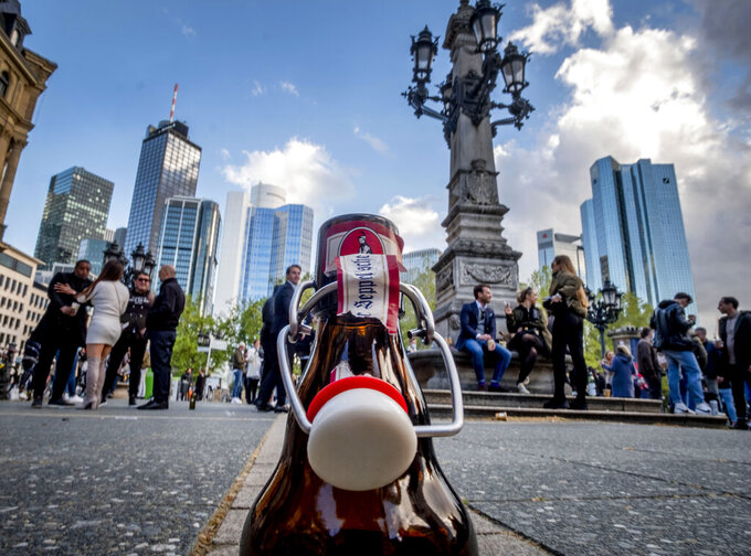 An empty beer bottle stands in front of the buildings of the banking district in Frankfurt, Germany, Friday, May 21, 2021. All people gathering on the square for drinks and food left when the police started checking if they are abiding by the coronavirus restrictions. (AP Photo/Michael Probst)
