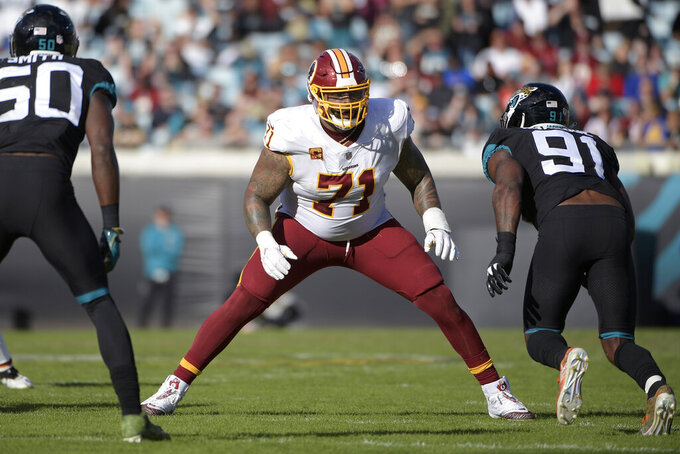 FILE - In this Dec. 16, 2018, file photo, Washington Redskins offensive tackle Trent Williams (71) sets up to block in front of Jacksonville Jaguars defensive end Yannick Ngakoue (91) during the second half of an NFL football game in Jacksonville, Fla. A person with knowledge of the situation says Williams has reported to the Redskins, ending his holdout. The person spoke to The Associated Press on condition of anonymity on Tuesday, Oct. 29, 2019, because the team had not announced Williams' return. He can be kept off the 53-man roster for up to three weeks after reporting. (AP Photo/Phelan M. Ebenhack, File)