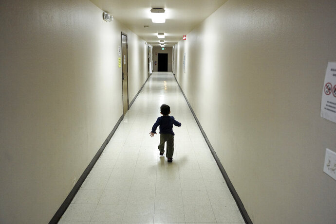 FILE - In this Dec. 11, 2018 file photo, an asylum-seeking boy from Central America runs down a hallway after arriving from an immigration detention center to a shelter in San Diego. Lawyers for eight immigrant families separated under Trump administration policy filed claims Monday, Feb. 11, 2019, against the U.S. government demanding $6 million each in damages for what they describe as lasting trauma. (AP Photo/Gregory Bull, File)