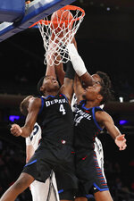 DePaul forward Paul Reed (4) and center Nick Ongenda (14) try to tip the ball in, with Xavier forward Jason Carter (25) and another Xavier player defending during the second half of an NCAA college basketball game in the first round of the Big East men's tournament Wednesday, March 11, 2020, in New York. DePaul won 71–67. (AP Photo/Kathy Willens)