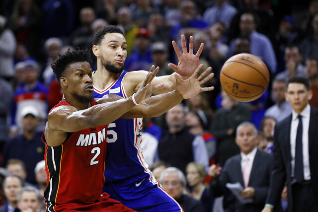 Philadelphia 76ers' Ben Simmons, right, and Miami Heat's Jimmy Butler reach for a pass during the second half of an NBA basketball game, Wednesday, Dec. 18, 2019, in Philadelphia. (AP Photo/Matt Slocum)