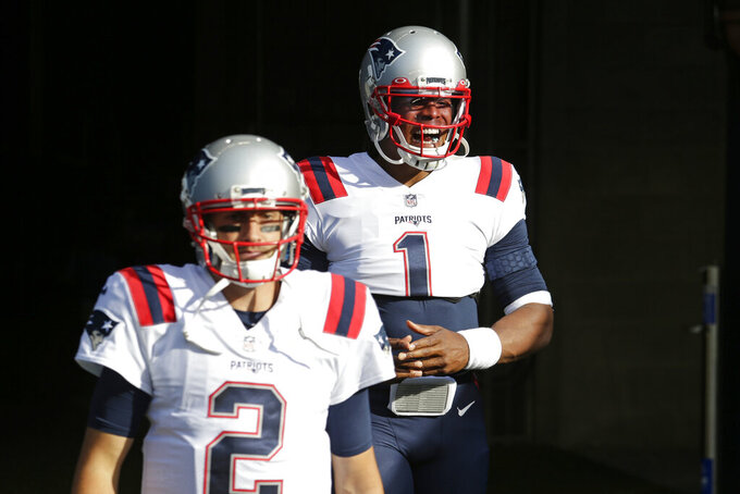 New England Patriots quarterback Cam Newton, right, and backup quarterback Brian Hoyer, left, walk out of the tunnel before an NFL football game against the Seattle Seahawks, Sunday, Sept. 20, 2020, in Seattle. (AP Photo/John Froschauer)