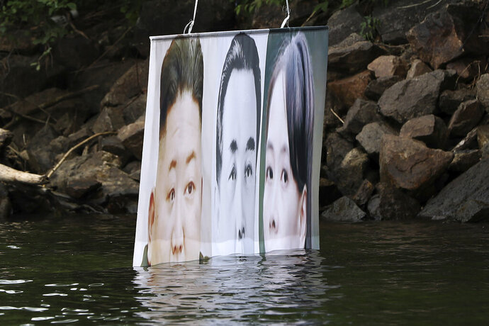 A banner with images of North Korean leader Kim Jong Un, left, the late leader Kim Il Sung, center, and Kim Yo Jong, the powerful sister of Kim Jong Un, released by Fighters For Free North Korea, is seen in Hongcheon, South Korea, Tuesday, June 23, 2020. A South Korean activist said Tuesday hundreds of thousands of leaflets had been launched by balloon across the border with North Korea overnight, after the North repeatedly warned it would retaliate against such actions. (Yang Ji-woong/Yonhap via AP)