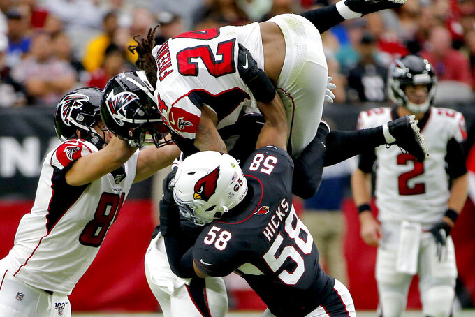 Atlanta Falcons running back Devonta Freeman (24) is hit by Arizona Cardinals middle linebacker Jordan Hicks (58) during the first half of an NFL football game, Sunday, Oct. 13, 2019, in Glendale, Ariz. (AP Photo/Rick Scuteri)