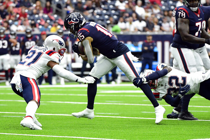 Houston Texans wide receiver Chris Moore (15) is tackled by New England Patriots safety Adrian Phillips (21) and safety Devin McCourty (32) during the first half of an NFL football game Sunday, Oct. 10, 2021, in Houston. (AP Photo/Justin Rex)