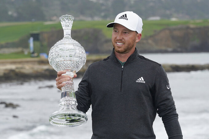 Daniel Berger holds up his trophy on the 18th green of the Pebble Beach Golf Links after winning the AT&T Pebble Beach Pro-Am golf tournament Sunday, Feb. 14, 2021, in Pebble Beach, Calif. (AP Photo/Eric Risberg)