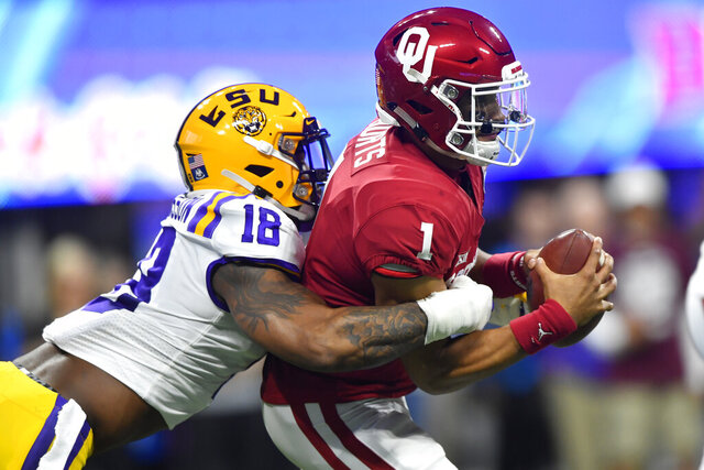 FILE - In this Dec. 28, 2019, file photo, LSU linebacker K'Lavon Chaisson (18) sacks Oklahoma quarterback Jalen Hurts (1) during the first half of the Peach Bowl NCAA semifinal college football playoff game in Atlanta. Chaisson was chosen by the Jacksonville Jaguars in the first round of the NFL draft Thursday, April 23, 2020.  (AP Photo/John Amis, File)