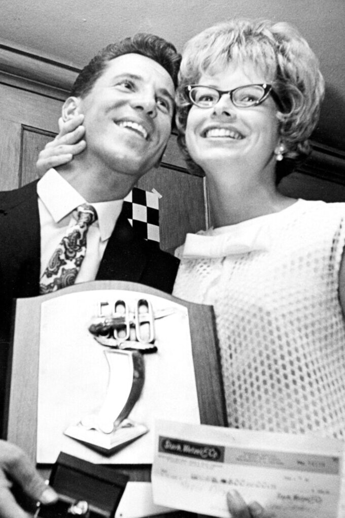 FILE - In this June 1, 1965, file photo, race driver Mario Andretti, left, of Nazareth, Pa., smiles with his wife Dee Ann after being named Rookie of the Year at Indianapolis following his third-place showing in the Indianapolis 500 the day before in Indianapolis, Ind. Mario feels the same pain as so many others these days. His wife died two years ago, long before the pandemic. And his beloved nephew lost a brutal battle with colon cancer. But then COVID-19 claimed his twin brother and one of the greatest racers of all time is not immune from the loneliness and depression sweeping the world.  (AP Photo/Bob Daugherty, File)