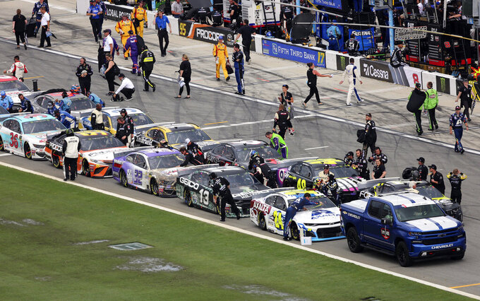 Pit crews begin to cover their cars on pit road as inclement weather moves in causing a delay in the NASCAR Cup Series auto race at Daytona International Speedway, Sunday, July 7, 2019, in Daytona Beach, Fla. (AP Photo/David Graham)