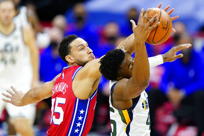 Philadelphia 76ers' Ben Simmons, left, and Utah Jazz's Donovan Mitchell reach for a loose ball during the first half of an NBA basketball game, Wednesday, March 3, 2021, in Philadelphia. (AP Photo/Matt Slocum)