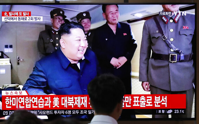 People watch a TV news program reporting North Korea's firing of projectiles with a file image of North Korean leader Kim Jong Un at the Seoul Railway Station in Seoul, South Korea, Saturday, Aug. 24, 2019. North Korea fired two suspected short-range ballistic missiles off its east coast on Saturday in the seventh consecutive week of weapons tests, South Korea's military said, a day after it threatened to remain America's biggest threat in protest of U.S.-led sanctions on the country. The Korean letters read: