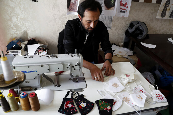 A tailor stitches Christmas face masks at a sewing workshop in Gaza City, Monday, Dec. 14, 2020. In the blockaded Gaza Strip, the Christmas season is giving a boost to Suhad Saidam's business that produces pandemic face masks decorated with holiday symbols. They also have provided a small boost several dozen families in a Palestinian enclave run by the Islamic militant Hamas group. (AP Photo/Adel Hana)