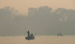 Men fish in the Cuiaba river amid smoke from fires at the Encontro das Aguas park at the Pantanal wetlands near Pocone, Mato Grosso state, Brazil, Sunday, Sept. 13, 2020. A vast swath of a vital wetlands is burning in Brazil, sweeping across several national parks and obscuring the sun behind dense smoke. (AP Photo/Andre Penner)