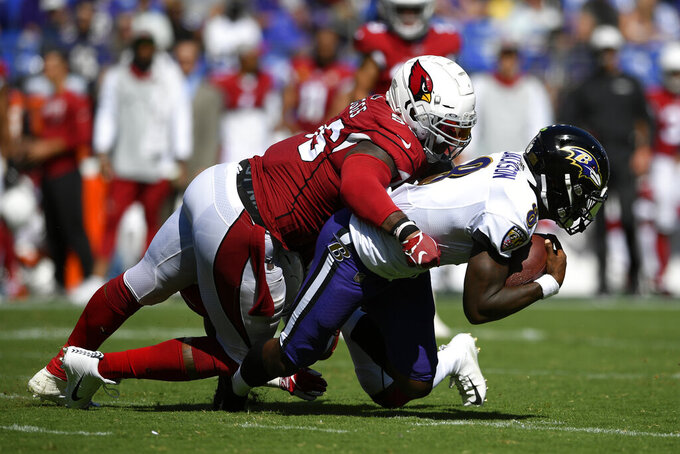 Arizona Cardinals outside linebacker Terrell Suggs, left, tackles Baltimore Ravens quarterback Lamar Jackson as Jackson rushes the ball in the second half of an NFL football game, Sunday, Sept. 15, 2019, in Baltimore. (AP Photo/Nick Wass)