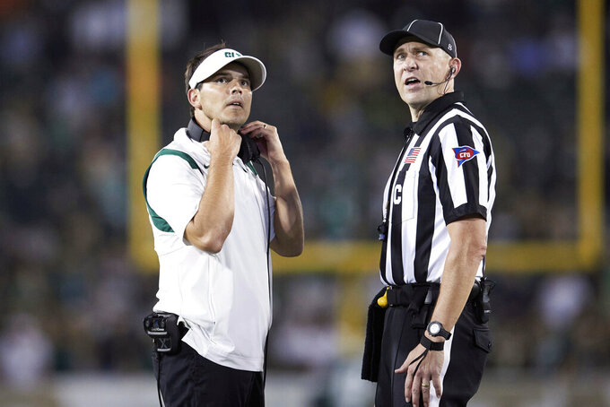Charlotte head coach Will Healy, left, and center judge Josh Fath look at the videoboard during during an NCAA college football game against Duke, Friday, Sept. 3, 2021, in Charlotte, N.C. (AP Photo/Brian Westerholt)