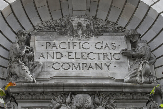 FILE - In this April 16, 2020, file photo, a Pacific Gas & Electric sign is displayed on the exterior of a PG&E building in San Francisco. When Pacific Gas & Electric set up emergency operations centers to coordinate intentional blackouts intended to prevent wildfires in Northern California, the nation's largest utility forgot one thing, emergency managers who knew the fundamentals of emergency management in California. (AP Photo/Jeff Chiu, File)