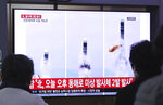 People watch a TV showing file images of North Korea's missile launch during a news program at the Seoul Railway Station in Seoul, South Korea, Thursday, Oct. 31, 2019. South Korea's military said North Korea on Thursday fired two projectiles toward its eastern sea, an apparent resumption of weapons tests aimed at ramping up pressure on Washington over a stalemate in nuclear negotiations. The sign reads:
